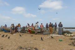 Att kontrollera för fiskare förtjänar på stranden royaltyfri bild