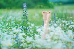 Att koppla av i naturkvinnan lägger benen på ryggen mellan blommabrunnsorten royaltyfria bilder