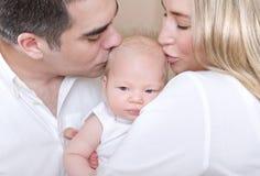 Att kyssa för barnföräldrar behandla som ett barn fotografering för bildbyråer