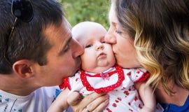 Att kyssa för föräldrar behandla som ett barn, bilden av en lycklig familj Arkivbilder