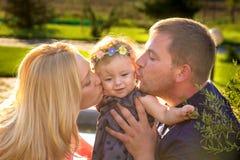 Att kyssa för föräldrar behandla som ett barn dottern arkivbilder