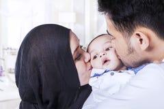 Att kyssa för farsa och för mamma behandla som ett barn kinder royaltyfri bild