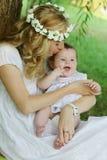Att kyssa för moder behandla som ett barn den utomhus- flickan Arkivbild