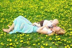 Att kyssa för moder behandla som ett barn i maskrosfält Royaltyfri Fotografi