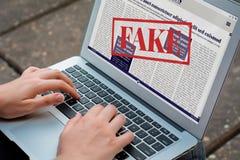Att läsa för ung kvinna som är digitalt, fejkar nyheterna på bärbara datorn arkivbild