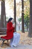 Att läsa i natur är min hobby, flicka med boken, och te sitter på bänken Royaltyfri Bild