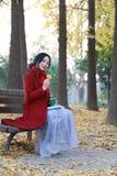 Att läsa i natur är min hobby, flicka med boken, och te sitter på bänken Royaltyfri Foto