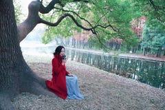 Att läsa i natur är min hobby, flicka med boken, och te sitter under stort lindträd Royaltyfri Fotografi