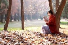 Att läsa i natur är min hobby, flickaläsebok utomhus royaltyfria bilder