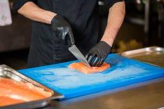 Att laga mat för tema är ett yrke av att laga mat Närbild av en Caucasian mans hand i ett restaurangkök som förbereder röda fiskf royaltyfria bilder