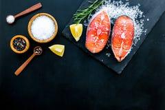 Att laga mat laxbiff från rå fisk på den svarta plattan med kryddor, rosmarin, citron och saltar på mörkt svart restaurangkök arkivbilder