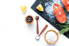 Att laga mat laxbiff från rå fisk på den svarta plattan med kryddor, rosmarin, citron och saltar på vitt restaurangkök arkivfoto