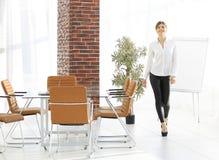 Att le assistenten för den unga kvinnan är rörande runt om kontoret Royaltyfri Fotografi