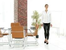 Att le assistenten för den unga kvinnan är rörande runt om kontoret Arkivfoton