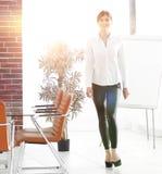 Att le assistenten för den unga kvinnan är rörande runt om kontoret Arkivbilder