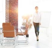 Att le assistenten för den unga kvinnan är rörande runt om kontoret Arkivfoto