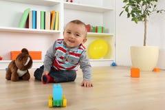 Att le behandla som ett barn barnet som spelar med leksaker Arkivfoton