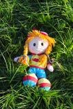 Att le behandla som ett barn - dockan som ligger i det gröna gräset Arkivfoto