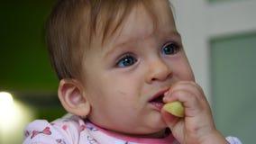 Att le behandla som ett barn flickan som äter äppleskivan av henne stock video
