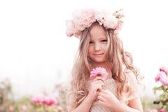 Att le behandla som ett barn flickan som poserar i rosträdgård Royaltyfri Fotografi