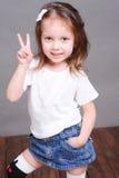 Att le behandla som ett barn flickan som poserar på grå färger Arkivfoto