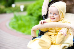 Att le behandla som ett barn flickasammanträde i en sittvagn Arkivfoto
