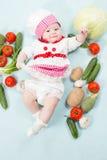 Att le behandla som ett barn ha på sig en kockhatt som omges av grönsaker Fotografering för Bildbyråer