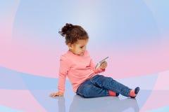 Att le behandla som ett barn lite flickan som spelar med smartphonen Royaltyfri Bild