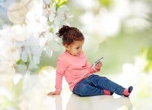 Att le behandla som ett barn lite flickan som spelar med smartphonen Royaltyfri Foto