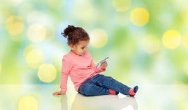 Att le behandla som ett barn lite flickan som spelar med smartphonen Royaltyfri Fotografi