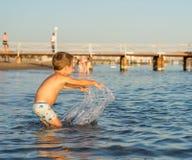 Att le behandla som ett barn lite pojken som spelar i havet Positiva mänskliga sinnesrörelser, känslor, Arkivfoton