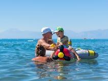 Att le behandla som ett barn pojken som spelar med farmodern och farfadern i havet på luftnivån Positiva mänskliga sinnesrörelser Royaltyfri Bild