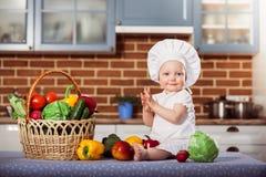 Att le behandla som ett barn toquen och förklädet för kock för iklädd vit för flicka Arkivbilder