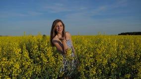 Att le brunettflickaanseende i fält av guling blommar och överför en kyss stock video