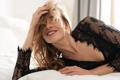 Att le brunettkvinnan ligger på säng inomhus royaltyfria foton