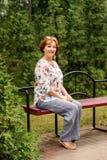 Att le den åldriga damen sitter på en bänk i grönskan parkerar i linnekläder arkivbilder