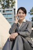 Att le den asiatiska affärskvinnan som använder mobiltelefonen och, sitter på trappa a royaltyfria bilder