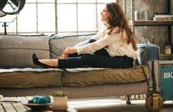 Att le den avkopplade unga kvinnan är avslappnande på soffan fotografering för bildbyråer