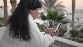 Att le den caucasian höga kvinnan är att skriva ett meddelande på smartphonen På terrassen av hotellet i en vit frottéämbetsdräkt lager videofilmer