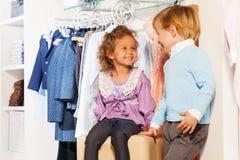 Att le den gulliga pojken ser flickan, medan shoppa Arkivbilder
