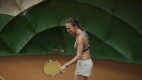 Att le, den lyckliga unga kvinnan i sportswear och långt hår gör en bred serveboll i tennis Starkt skott långsam rörelse lager videofilmer