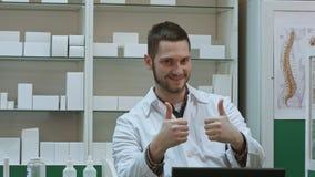 Att le den manliga apotekaren i den vita lagvisningen tummar upp och okeyhandgesten Arkivfoto