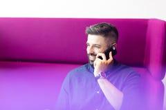 Att le den mitt- vuxna affärsmannen som talar på mobiltelefonen, medan sitta på lilor, uttrycker på kontoret royaltyfri fotografi