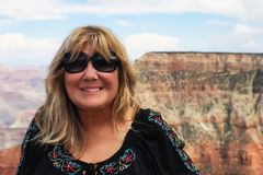 Att le den nätta mitt åldrades den kvinnliga turisten i den färgrika blusen po arkivfoto