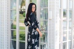 Att le den trendiga flickan i siden- kläder som väntar på hennes vänner på verandan av restaurangen, önskar att möta så royaltyfri fotografi