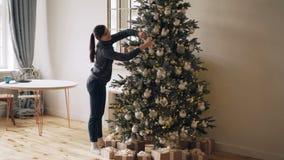 Att le den unga damen är upptaget att dekorera gran-trädet för ferier för det nya året som trycker på bollar, leksaker, ljus och  lager videofilmer