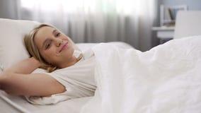 Att le den unga damen som ligger i säng, ordnar till för ny dag, inspirerat och motiverat royaltyfri foto