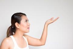 Att le den unga kvinnan är att peka på kopieringsutrymme Fotografering för Bildbyråer