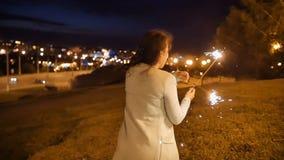 Att le den unga kvinnan står på en hög kulle med tomteblosset med stadsnattsikt på bakgrund arkivfilmer