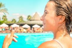 Att le enjoing sommarsemester för tonårig flicka på hotellpölen med gömma i handflatan och solparaplyer på bakgrunden royaltyfria foton